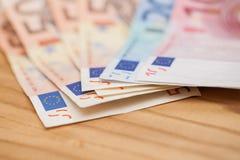 Haufen von Eurobanknoten auf einem Holztisch Lizenzfreie Stockfotos