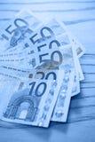 Haufen von Eurobanknoten auf einem Holztisch Lizenzfreie Stockbilder