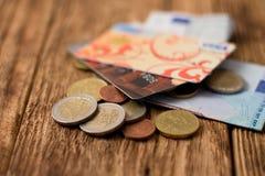 Haufen von Eurorechnungen und von Münzen mit zwei Kreditkarten Lizenzfreies Stockfoto