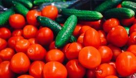 Haufen von ganzen nassen Tomaten und von Gurken Spitzenstandpunkt, voller Rahmen Stockbild
