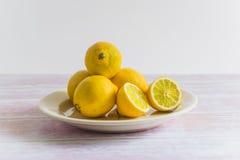 Haufen von gelben Zitronen auf einer Platte Stockbilder
