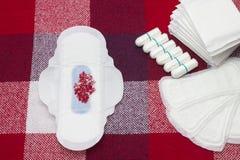 Haufen von gesundheitlichen weichen Auflagen der Menstruation mit roten Perlen und von Baumwolltampon für Frauenhygieneschutz Kri stockfotografie