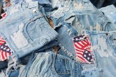 Haufen von heftigen und ausgefransten, abgenutzten Jeans Lizenzfreies Stockfoto