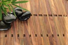 Haufen von heißen Steinen des Badekurortes auf hölzernem Hintergrund Stockbilder