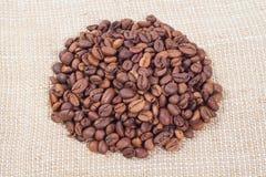 Haufen von Kaffeebohnen auf Hintergrund von Leinwand Lizenzfreie Stockbilder