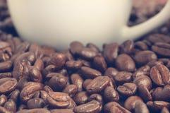 Haufen von Kaffeebohnen und von Teil der Kaffeetasse an der Hintergrundweinlese gefiltert Lizenzfreies Stockbild