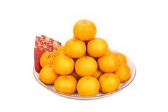 Haufen von Mandarinen, rote Pakete mit Charakter des guten Glücks Stockfotografie