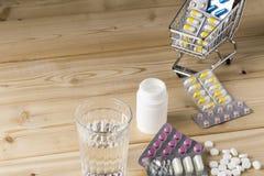 Haufen von Medizinpillen Blisterpackung und von Wasserglas Lizenzfreies Stockbild