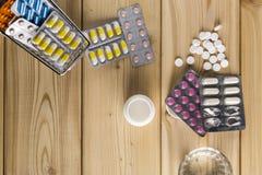 Haufen von Medizinpillen Blisterpackung und von Wasserglas Lizenzfreie Stockfotos