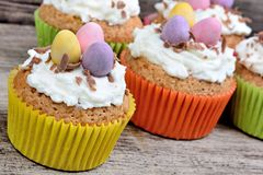 Haufen von Muffins mit Schokoladeneiern auf alter Tabelle Lizenzfreie Stockfotos
