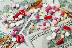 Haufen von pharmazeutischen Drogen- und Medizinpillen zerstreute auf Dollarbargeld, Kostenarzneimittel und Behandlungskonzept Lizenzfreies Stockfoto