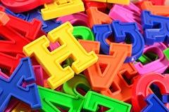Haufen von Plastik farbigem nahem hohem der Alphabetbuchstaben Stockfotografie