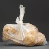 Haufen von reifen Kartoffeln im klaren Behälter auf weißem Hintergrund Stockfoto