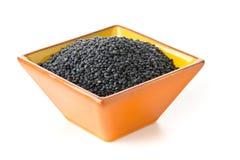 Haufen von schwarzen organischen Weißwallinsen in orange Terrakottaschüssel O lizenzfreie stockbilder