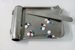 Haufen von verschiedenen Pillen, Tabletten, die in die rostfreie Platte gießen Stockbilder