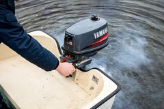 Haugesund Norge - januray 10, 2018: Man att starta Yamaha en utombords- motor på ett plast- fartyg, avgasrörrök från fotografering för bildbyråer