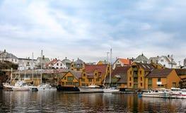 Haugesund, Norvegia - 9 gennaio 2018: Vecchie case di legno sull'isola Risoy, sulle barche e sulle costruzioni di industria della immagine stock