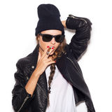 Haughty girl in sunglasses and black leather jacket smoking cigar Royalty Free Stock Photography