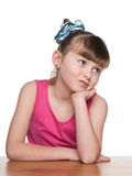 Haughty little girl at a school desk. A haughty little girl sits at a school desk against the white background Stock Photo