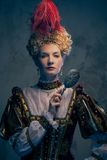 Haughty queen. In royal dress with mirror Stock Image