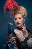 Haughty queen. In royal dress with mirror Stock Photography