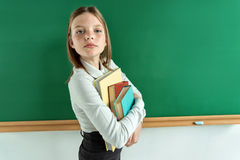 Haughty student hugging books. Photo of teen near blackboard, education concept Stock Photos