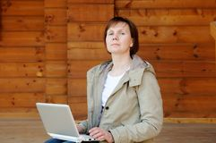 Haughty woman with laptop. Sitting on wooden porch Royalty Free Stock Photo