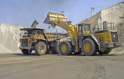 Hauler and loader action. Loading sand with a Komatsu loader into a Cat 85 ton hauler at a stone quarry Royalty Free Stock Photos