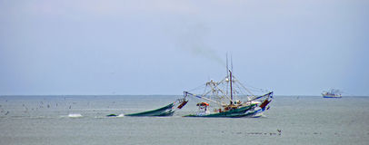Hauling in the Nets. A photograph of shrimp boats off the coast of Edisto Island in the Atlantic Ocean hauling in their nets with the catch of the day Royalty Free Stock Photos