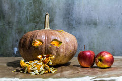 Haunted carved pumpkins for Halloween with apple Royalty Free Stock Photo