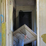 Haunted hallway. Ghost and unhinged door in the haunted hallway of an abandoned house stock image