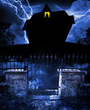 Haunted house. A large black scary house looms in the distance with a silhouette of a woman standing in the only light from the house.  Concept for halloween Royalty Free Stock Image
