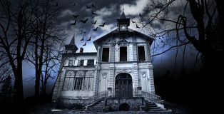 Haunted House. With dark scary horror atmosphere around it. Blue dark sky trees silhouettes and bats coming out of the windows royalty free stock image