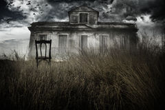 Haunted house and chair. Abandoned chair out in a field facing a haunted house royalty free stock photo