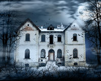 Haunted House. With dark scary horror atmosphere around it. Blue dark sky trees silhouettes and bats coming out of the windows royalty free stock photos
