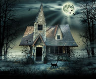 Haunted House. With dark scary horror atmosphere around it. Grey dark sky trees silhouettes and bats coming out of the windows.A black cat walking infront of Stock Photo