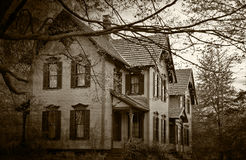 Haunted house in dark sepia. Old house with trees in dark sepia tones and vignetting Royalty Free Stock Photography
