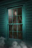 Haunted House Ghost, Dead Woman. The ghost of a beautiful young dead woman looks out the window of a Halloween haunted House royalty free stock images