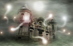 Haunted house. Glowing spirits circling old house in mist Royalty Free Stock Photo