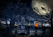Haunted House with Jack-O-Lantern. An old stone and iron fence with flame lanterns and jack-o-lantern on stone pillar, iron gate is open leading to haunted house royalty free stock images