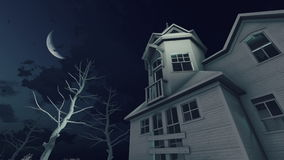 Haunted house and night sky 4K time lapse. Old abandoned haunted house and creepy dead trees under dark night sky with big half moon and fast moving clouds. Low stock video