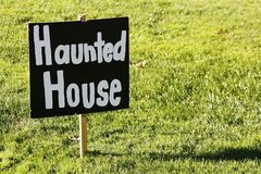 Haunted house sign in a sunny day. Sunny day haunted house sign on shinny grass Stock Photos