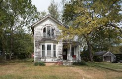 Haunted House with Trees. Abandoned Haunted House with Trees and Chair on front Porch. Paint is peeling off the facade stock images