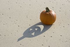 Haunted Pumpkin. Pumpkin on the sand with face cut out of the shadow royalty free stock image