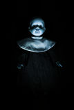Haunting Child's Doll Figure. Emerging from a dark, shadowy background Royalty Free Stock Photos