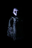 Haunting Child's Doll Figure. Emerging from a dark, shadowy background Royalty Free Stock Image