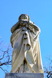 Haunting Statue of a lady or angel in a white robe standing as i. F guarding over and watching Stock Images