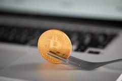 Haupt-cryptocurrency goldener bitcoin Griff auf einer Gabel auf einem silbernen Laptop, unscharfer Hintergrund Stockbilder