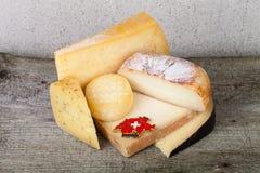Haupt- und verschiedene Stücke Käse auf einem Holztisch Lizenzfreie Stockbilder