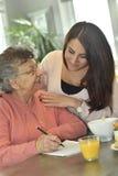 Hauptbetreuer, welche einer älteren Dame mit Kreuzworträtseln hilft lizenzfreies stockfoto
